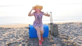 Jovem mulher feliz em férias com uma mala de viagem que mostra os polegares acima filme