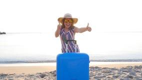 Jovem mulher feliz em férias com uma mala de viagem que mostra os polegares acima vídeos de arquivo