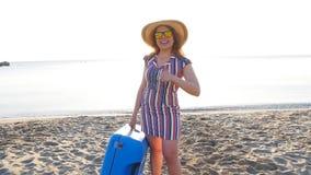 Jovem mulher feliz em férias com uma mala de viagem que mostra os polegares acima video estoque