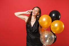 Jovem mulher feliz em pouco vestido preto que guarda balões de ar que fala no telefone celular, conversação agradável de condução imagens de stock