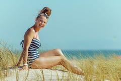 Jovem mulher feliz em roupa de banho listrado que senta-se no litoral imagem de stock