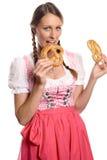 Jovem mulher feliz em um dirndl que come pretzeis Imagens de Stock