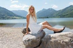 Jovem mulher feliz em um lago nas montanhas Imagens de Stock