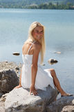 Jovem mulher feliz em um lago nas montanhas Imagens de Stock Royalty Free