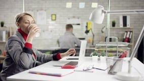 Jovem mulher feliz engraçada que canta ao escutar a música alta nos fones de ouvido que sentam-se na mesa de escritório com portá vídeos de arquivo