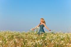 A jovem mulher feliz na calças de ganga sundress salta no campo dos camomiles em um dia ensolarado Imagem de Stock