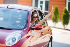 Jovem mulher feliz na condução de carro na estrada Fotografia de Stock