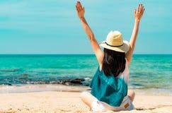 A jovem mulher feliz na forma do estilo ocasional e o chapéu de palha sentam-se na praia da areia Relaxando e para apreciar o fer fotos de stock royalty free