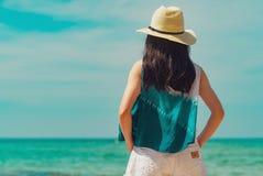 Jovem mulher feliz na forma do estilo ocasional e na posição do chapéu de palha na praia do mar Relaxando e para apreciar o feria fotografia de stock royalty free