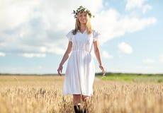 Jovem mulher feliz na grinalda da flor no campo de cereal Imagens de Stock