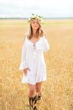 Jovem mulher feliz na grinalda da flor no campo de cereal Fotografia de Stock