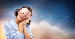 Jovem mulher feliz na m?scara do sono do pijama e do olho foto de stock royalty free