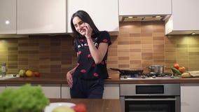 A jovem mulher feliz na roupa home está falando com um amigo no telefone e está cozinhando um café da manhã em casa faz a filme
