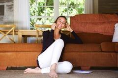 Jovem mulher feliz na sala de visitas usando o telefone celular Imagens de Stock Royalty Free