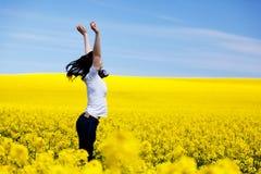 Jovem mulher feliz no campo da mola Sucesso Imagens de Stock Royalty Free