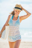 Jovem mulher feliz no chapéu e com saco que anda na praia Fotos de Stock