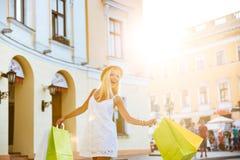 Jovem mulher feliz no chapéu que guarda sacos de compras ao andar imagem de stock royalty free