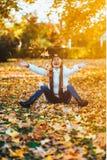 A jovem mulher feliz no parque no dia ensolarado do outono, rir, jogando sae Menina bonita alegre na camiseta branca durante o SE foto de stock