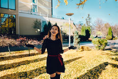 A jovem mulher feliz no parque no dia ensolarado do outono, rir, jogando sae Menina bonita alegre no fashi retro preto do outono  foto de stock