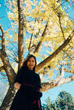 A jovem mulher feliz no parque no dia ensolarado do outono, rir, jogando sae Menina bonita alegre no fashi retro preto do outono  fotos de stock