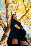 A jovem mulher feliz no parque no dia ensolarado do outono, rir, jogando sae Menina bonita alegre no fashi retro preto do outono  fotografia de stock