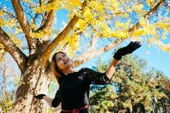 A jovem mulher feliz no parque no dia ensolarado do outono, rir, jogando sae Menina bonita alegre no fashi retro preto do outono  fotografia de stock royalty free