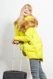 Jovem mulher feliz no revestimento morno com mala de viagem Fotos de Stock