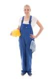 Jovem mulher feliz no uniforme azul do construtor que guarda o capacete amarelo imagens de stock