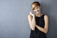 Jovem mulher feliz no vestido e em pérolas pretos