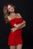 Jovem mulher feliz no vestido vermelho sobre o fundo preto Imagem de Stock Royalty Free