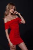 Jovem mulher feliz no vestido vermelho sobre o fundo preto Fotografia de Stock