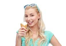 Jovem mulher feliz nos óculos de sol que come o gelado Imagens de Stock Royalty Free
