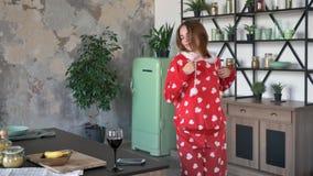 Jovem mulher feliz nos pijamas que dançam e que sorriem, cozinha extravagante vestindo da capa, a alegre e a engraçada, a moderna vídeos de arquivo