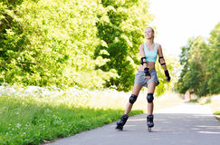 Jovem mulher feliz nos rollerblades que montam fora Imagem de Stock