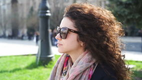 A jovem mulher feliz nos vidros senta-se em um banco na cidade video estoque
