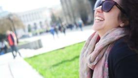 A jovem mulher feliz nos vidros senta-se em um banco na cidade vídeos de arquivo
