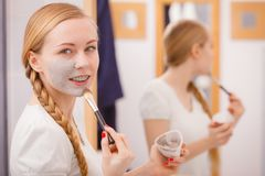 Jovem mulher feliz que aplica a máscara da lama na cara imagem de stock