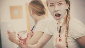 Jovem mulher feliz que aplica a máscara da lama na cara fotografia de stock royalty free