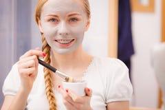 Jovem mulher feliz que aplica a máscara da lama na cara imagens de stock
