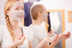 Jovem mulher feliz que aplica a máscara da lama na cara fotos de stock royalty free