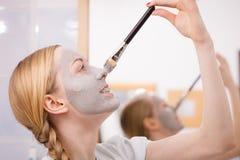 Jovem mulher feliz que aplica a máscara da lama no nariz fotografia de stock