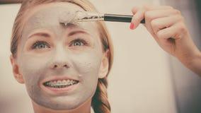 Jovem mulher feliz que aplica a m?scara da lama na cara foto de stock royalty free