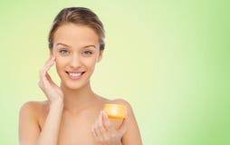 Jovem mulher feliz que aplica o creme a sua cara Fotos de Stock