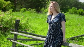 Jovem mulher feliz que aprecia o sol que senta-se na cerca de madeira na natureza do campo acima da grama verde agradável filme
