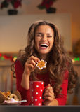 Jovem mulher feliz que aprecia petiscos do Natal na cozinha foto de stock