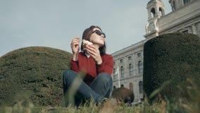 Jovem mulher feliz que aprecia um gelado que senta-se na grama no parque em Sunny Day Imagens de Stock Royalty Free