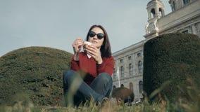 Jovem mulher feliz que aprecia um gelado que senta-se na grama no parque em Sunny Day Fotografia de Stock