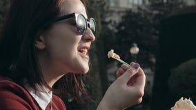 Jovem mulher feliz que aprecia um gelado que senta-se na grama no parque em Sunny Day Imagens de Stock