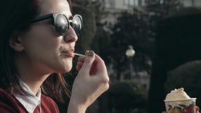 Jovem mulher feliz que aprecia um gelado que senta-se na grama no parque em Sunny Day Imagem de Stock