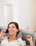 Mulher feliz que coloca no divã e no telemóvel de fala imagens de stock